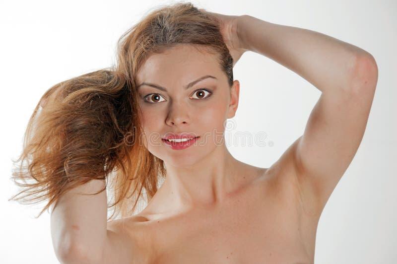 Ung nätt kvinna som rymmer hennes långa hår fotografering för bildbyråer