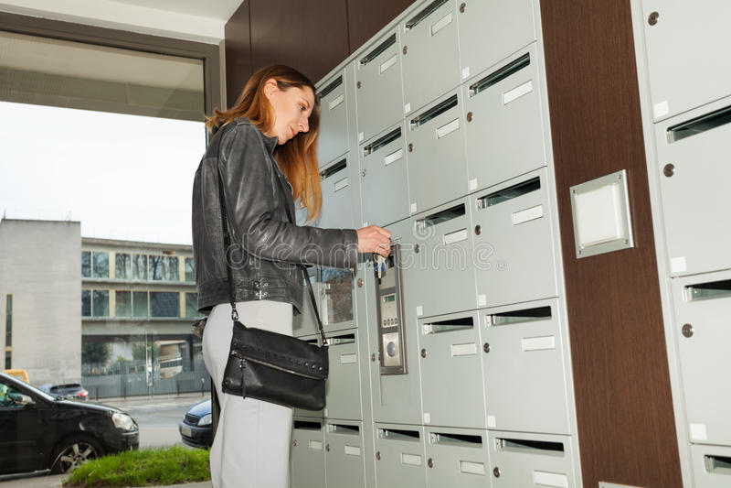Ung nätt kvinna som stänger hennes brevlåda med en tangent arkivfoto