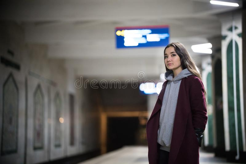 Ung nätt kvinna som väntar på drevet i gångtunnelplattform royaltyfri foto