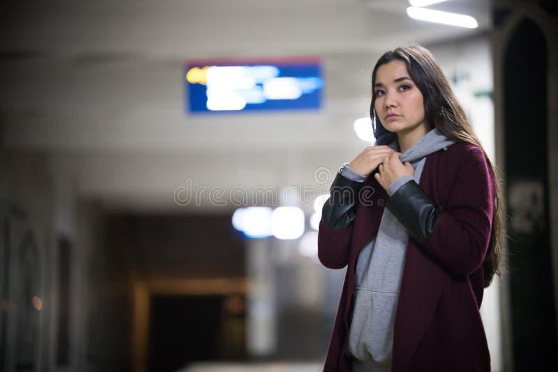 Ung nätt kvinna som väntar på drevet i gångtunnelplattform natt arkivbild