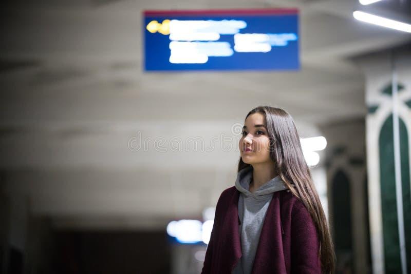 Ung nätt kvinna som väntar på drevet i gångtunnelplattform natt le royaltyfri bild