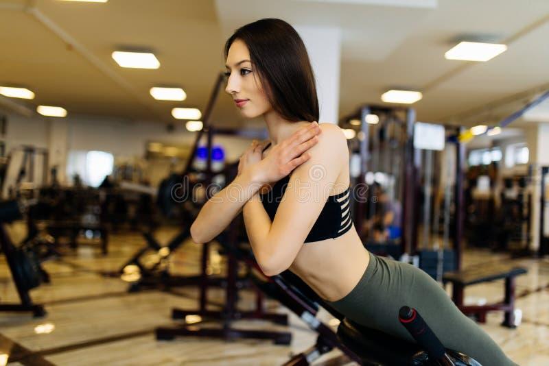 Ung nätt kvinnagenomkörare på övningsmaskinen i konditionidrottshall fotografering för bildbyråer