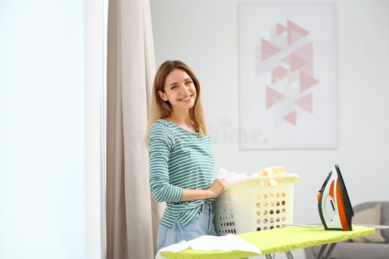 Ung nätt kvinnainnehavkorg av den rena tvätterit på strykbrädan fotografering för bildbyråer