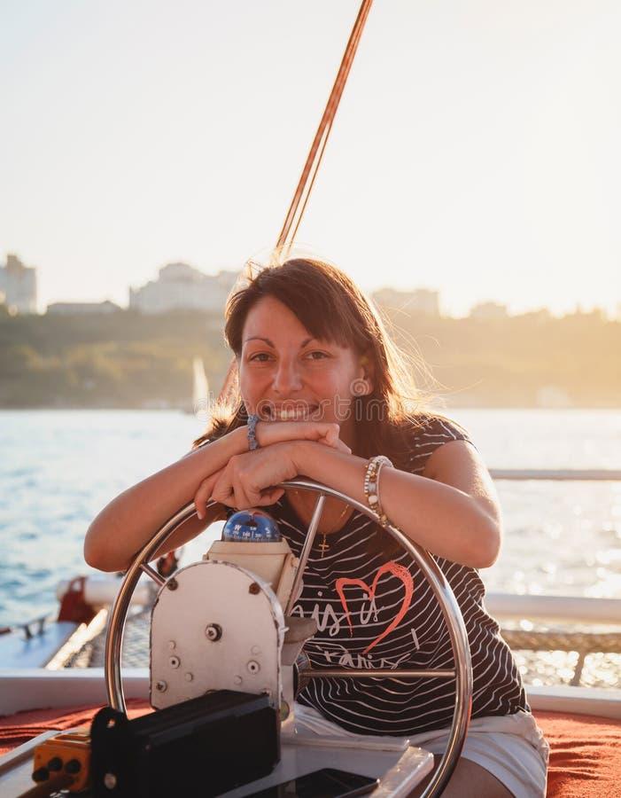 Ung nätt le kvinna i randig skjorta och vita kortslutningar som kör den lyxiga yachten i havet, varm sommardag, solnedgång arkivbild