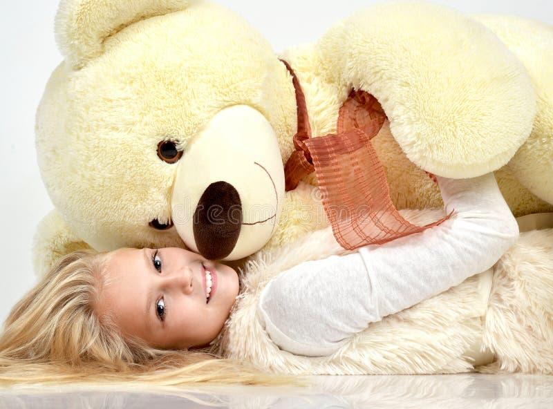 Ung nätt lycklig krama stor nallebjörn för tonårs- flicka som ler s arkivfoto