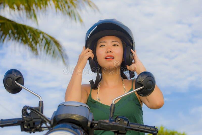 Ung nätt lycklig och gullig asiatisk kinesisk kvinna som justerar motorcykelhjälmridning på sparkcykelmopeden som in isoleras på  fotografering för bildbyråer