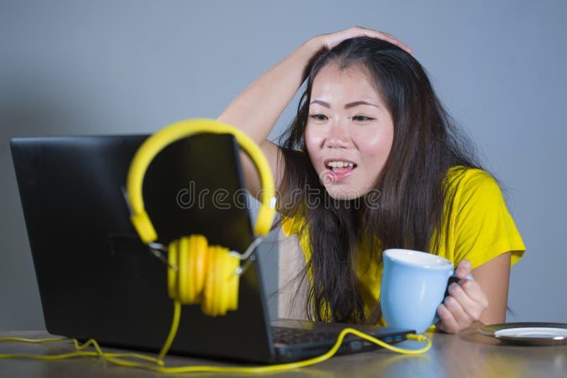Ung nätt och lycklig asiatisk koreansk kvinna på skrivbordet som tycker om internet på bärbar datordatoren som ler att se förvåna arkivbild