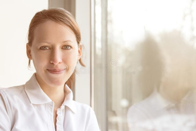 Ung nätt sjuksköterska framme av ett fönster, med reflexion royaltyfri foto