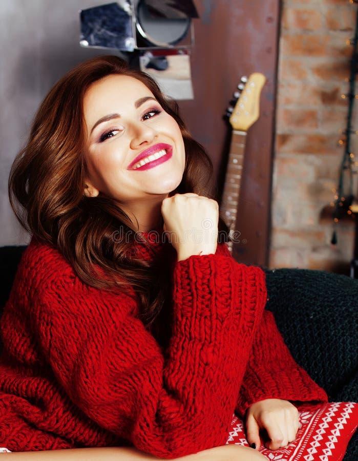 Ung nätt stilfull kvinna i röd vintertröja på soffan i lyckligt le för hemmiljö, livsstilfolkbegrepp arkivbilder