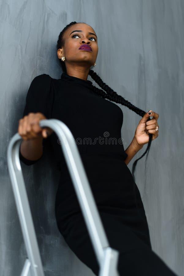 Ung nätt svart amerikansk kvinna som trycker på hennes tjocka fläta som ser upp på mörk studiobakgrund arkivfoton