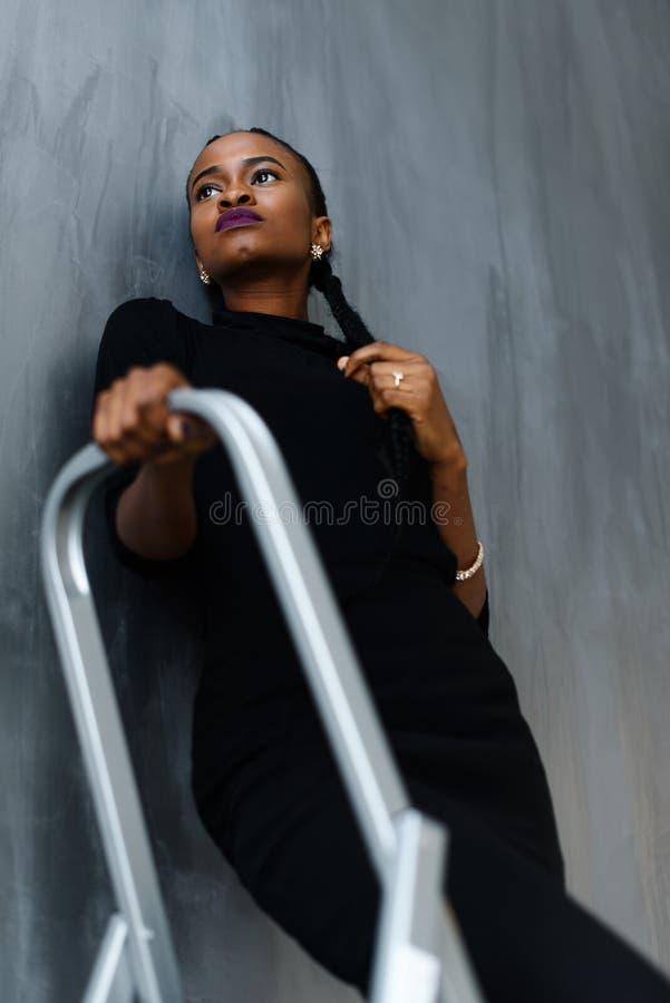 Ung nätt svart amerikansk kvinna som trycker på hennes tjocka fläta som ser upp på mörk studiobakgrund arkivfoto