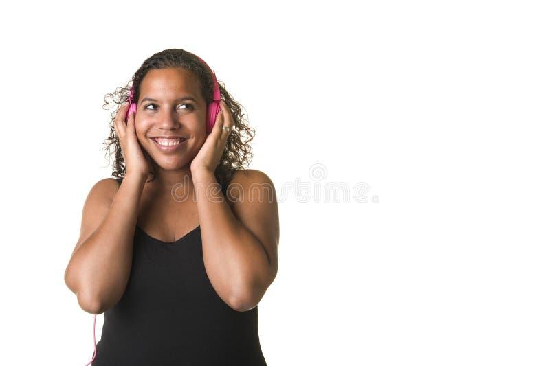 Ung nätt svart kvinna som lyssnar till musik på en rosa headphone royaltyfri foto