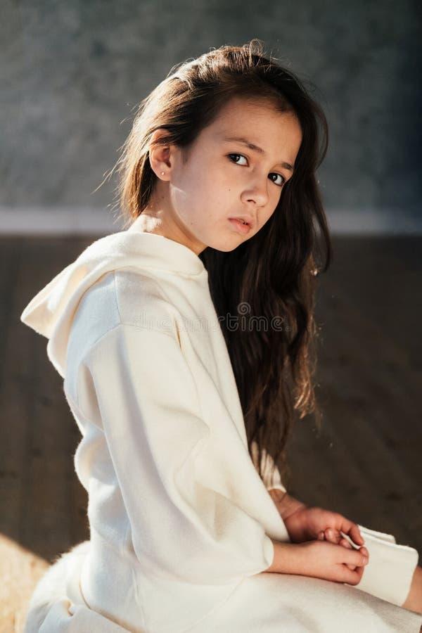 Ung nätt tonårs- flicka med ledsna sinnesrörelser Barnflicka i den vita klänningen som ser kameran tät stående upp fotografering för bildbyråer