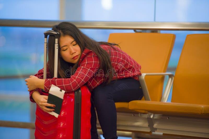Ung nätt trött och utmattad asiatisk koreansk turist- kvinna i flygplats som sover uttråkat sammanträde på korridoren för logipor arkivfoto