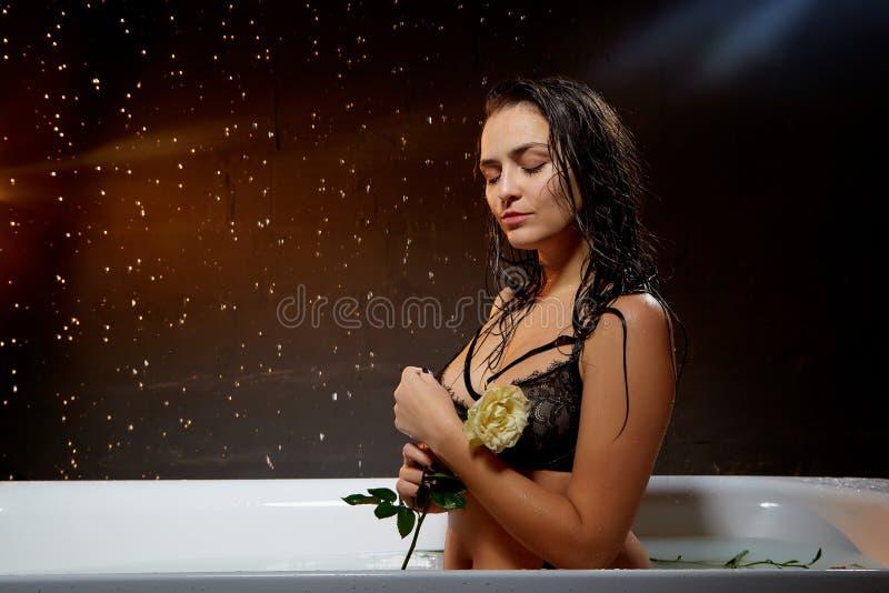 Ung n?tt brunettkvinna i bad med vatten och f?rgst?nk och droppar i ett m?rkt rum royaltyfria foton