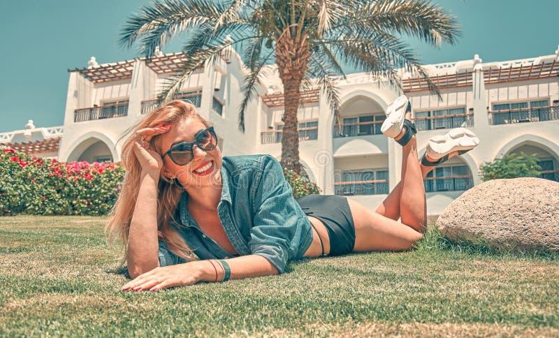 Ung n?tt kvinna som ligger p? gr?set p? sommarsolnedg?ngen Naturlig lycka, gyckel och harmoni arkivfoton