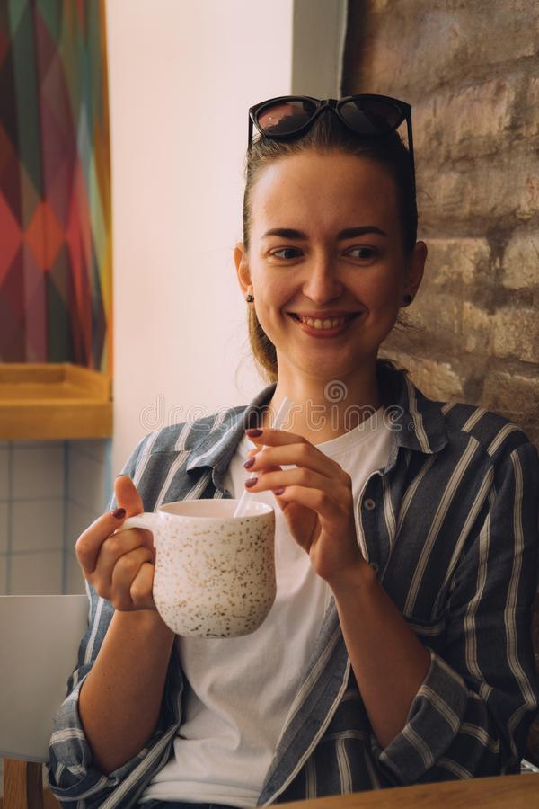 Ung n?tt kvinna som sitter i ett kaf? och talar p? telefonen Flickan dricker varmt kaffe arkivbild