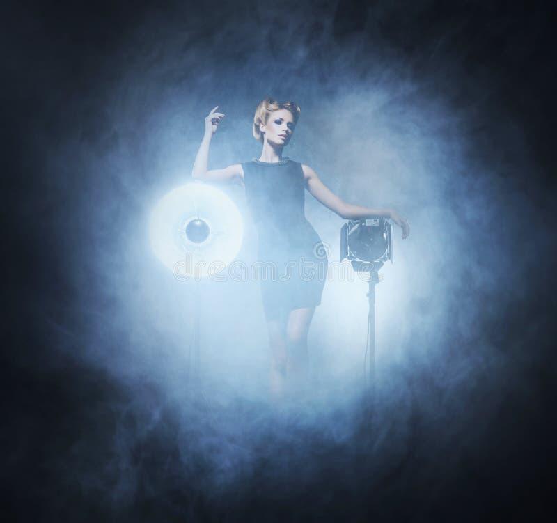 Ung och emotionell kvinna i modeklänning över glamourbackgrou royaltyfri bild