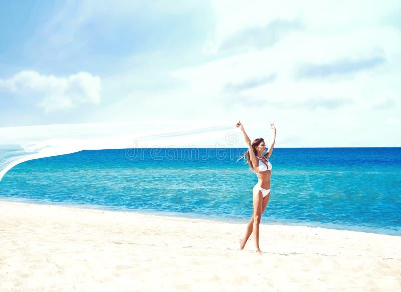 Ung och härlig flicka i den vita baddräkten som poserar på stranden royaltyfri bild