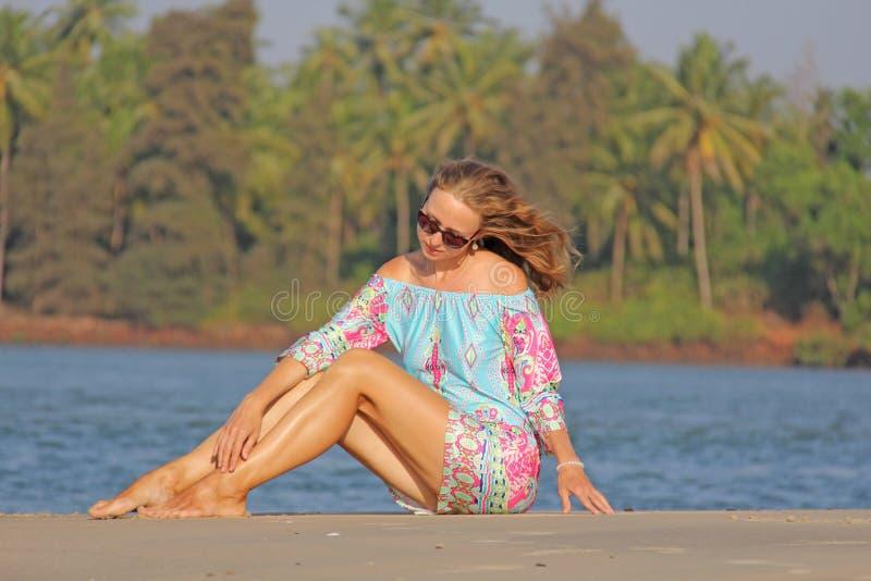 Ung och härlig flicka med blont hår, i korta blått och rosa färger royaltyfri foto