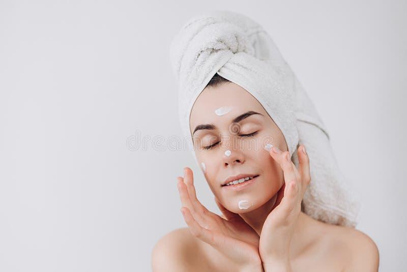 Ung och härlig flicka som använder en produkt, en fuktighetsbevarande hudkräm eller en lotion för hudomsorg som tar omsorg av hen royaltyfri bild