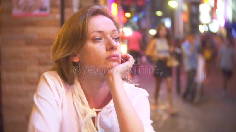 Ung och härlig kvinna som sitter på gatan i ett kafé eller en terrass En kvinna håller ögonen på att promenera för förbipasserand arkivfoton