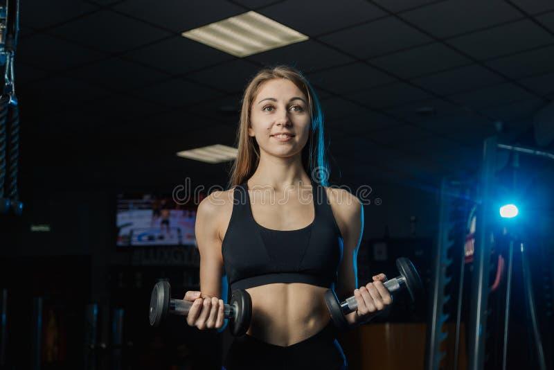 Ung och härlig kvinna som utarbetar med hantlar i idrottshall Bicepskrullning royaltyfri bild