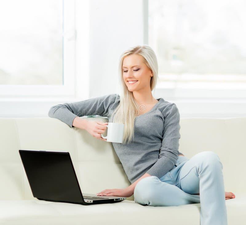 Ung och lycklig kvinna som vilar på den hemmastadda soffan och dricker kaffe royaltyfri bild