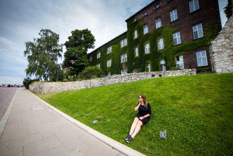 Ung och lycklig kvinnaturist som går på den Wawel slotten i den gamla europeiska staden Krakow, Polen Resor runt om Europa royaltyfria foton