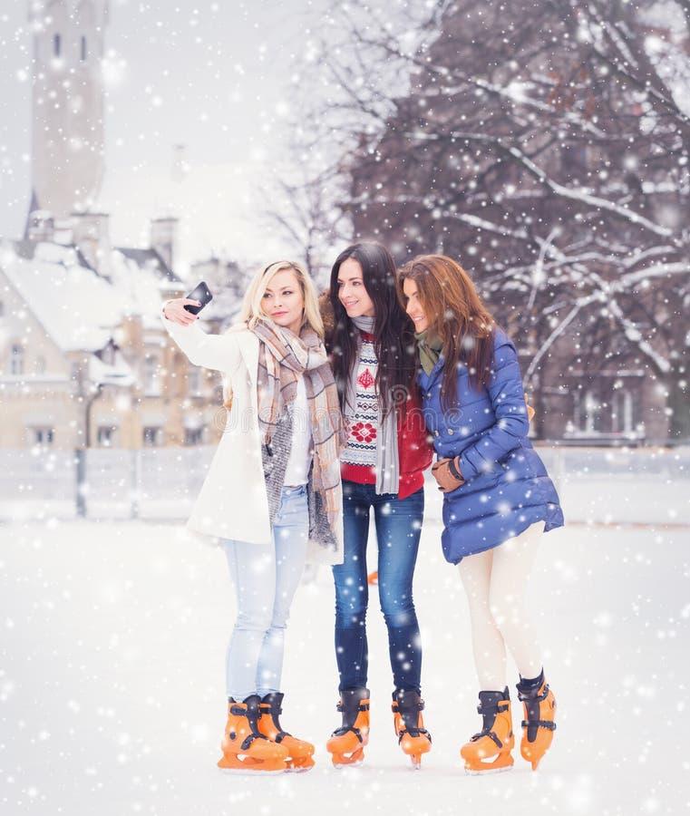 Ung och nätt flicka som åker skridskor på utomhus- is-isbana för öppen luft på wi arkivbild