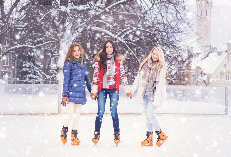 Ung och nätt flicka som åker skridskor på utomhus- is-isbana för öppen luft på wi royaltyfri bild