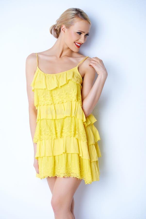 Sexig blond kvinna i gul klänning arkivbilder