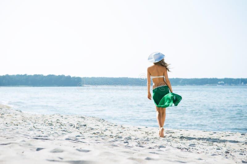 Ung och sexig kvinna som poserar i en hatt på stranden royaltyfria bilder