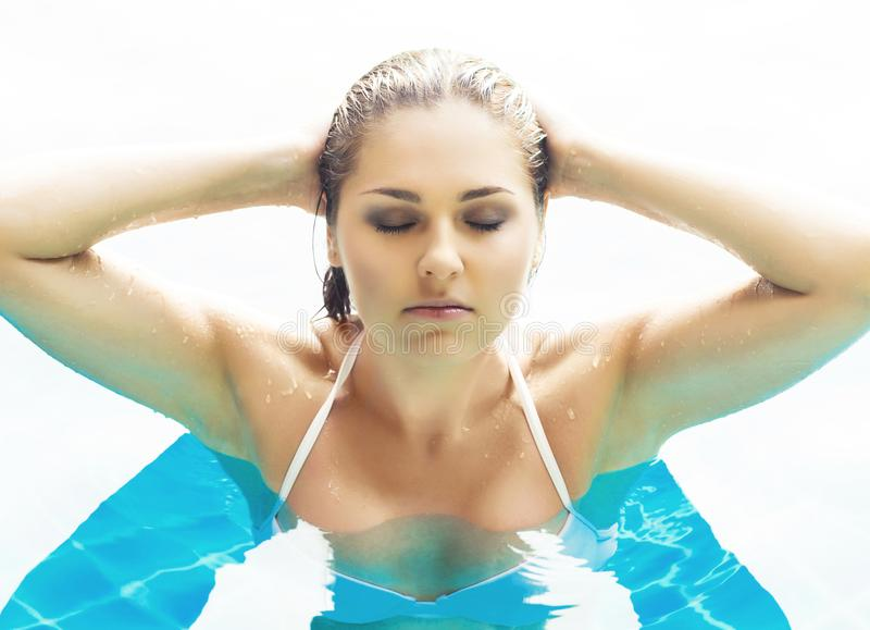 Ung och sportig kvinna i baddräkt Flicka som kopplar av i en pöl på sommar royaltyfri bild