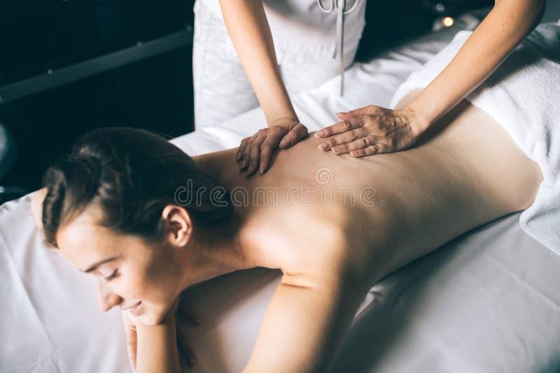Ung och sund kvinna i den Spa salongen Traditionell terapi för svensk massage royaltyfri bild