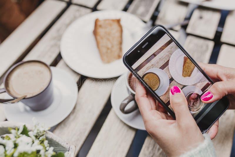 Ung oigenkännlig kvinna som tar en bild med mobiltelefonen av hennes frukost, en kopp kaffe och ett stycke av kakan frukost arkivfoto