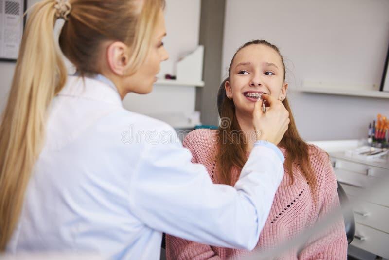 Ung orthodontist som kontrollerar patienten i tandläkares kontor royaltyfri fotografi