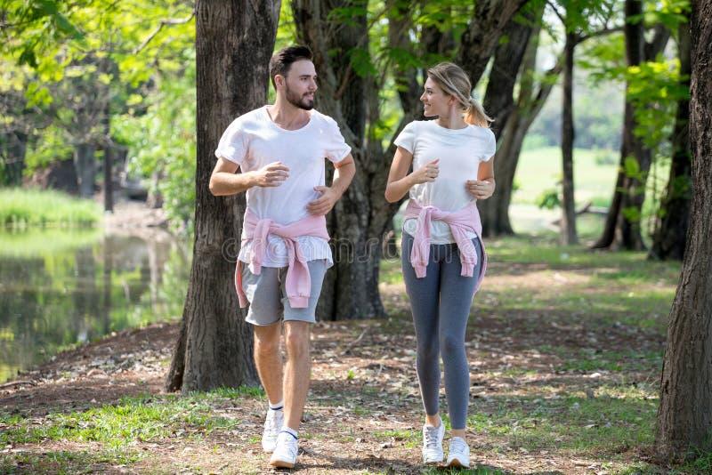 ung parkondition i sportswearen som tillsammans kör parkerar in sportman och kvinna som utomhus joggar i natur genomkörare som öv royaltyfria foton