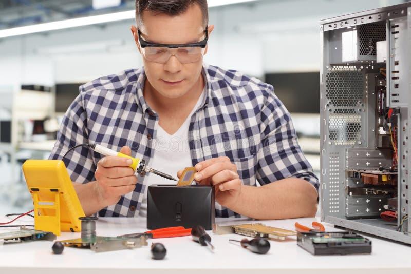 Ung PCtekniker som löder en chip royaltyfri foto