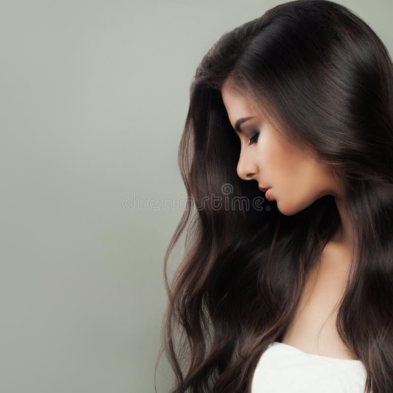 Ung perfekt brunettkvinnastående Långt mörkt sunt hår och naturlig makeup Begrepp för håromsorg royaltyfri fotografi