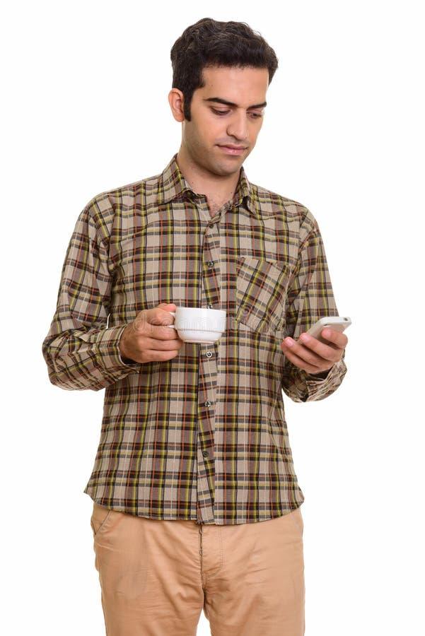Ung persisk man som använder mobiltelefonen, medan rymma kaffekoppen royaltyfri foto