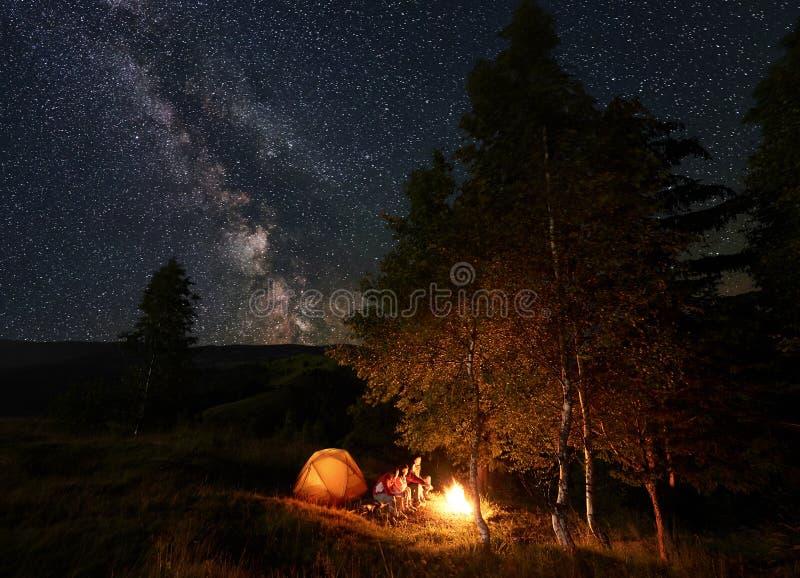 Ung peson vid lägereldsammanträde på journaler under natten som campar bland träd, near tältet under stjärnklar himmel royaltyfri bild