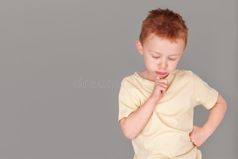Ung pojke för brännhet rödhårig man i gul skjorta i finger till hakan i djup tänkt slagställning royaltyfri fotografi