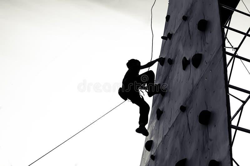 Ung pojke för fritt klättrarebarn som öva på konstgjorda stenblock arkivfoto