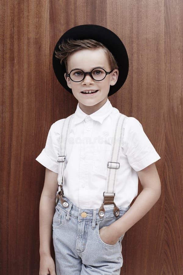 Ung pojke för ståendeofa på träbakgrund arkivfoton