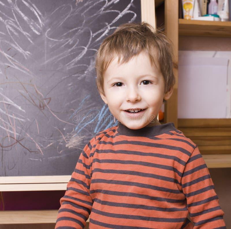 Ung pojke framme av svart tavla royaltyfri foto