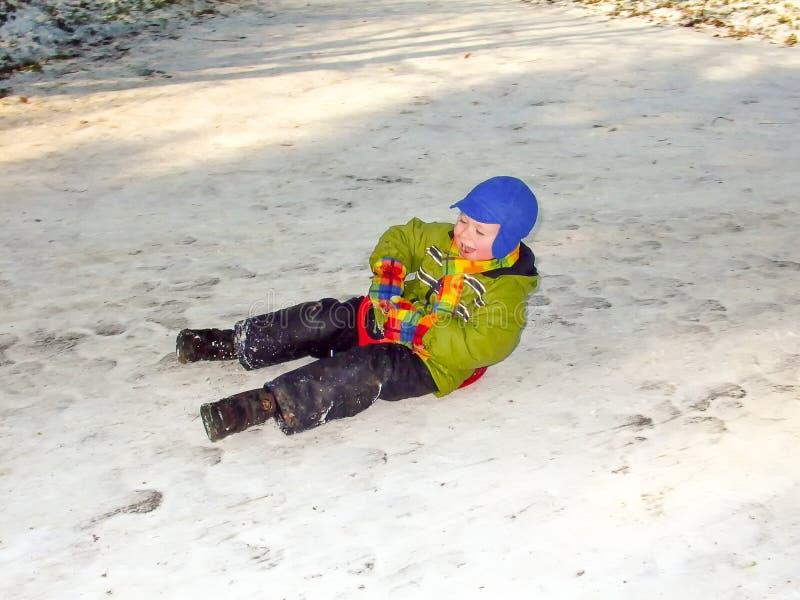 Ung pojke gillar att halka på den vita snön fotografering för bildbyråer