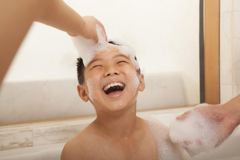 Ung pojke i bubbelbad arkivfoto