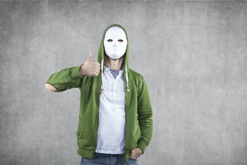 Ung pojke i en maskering med en tumme upp fotografering för bildbyråer