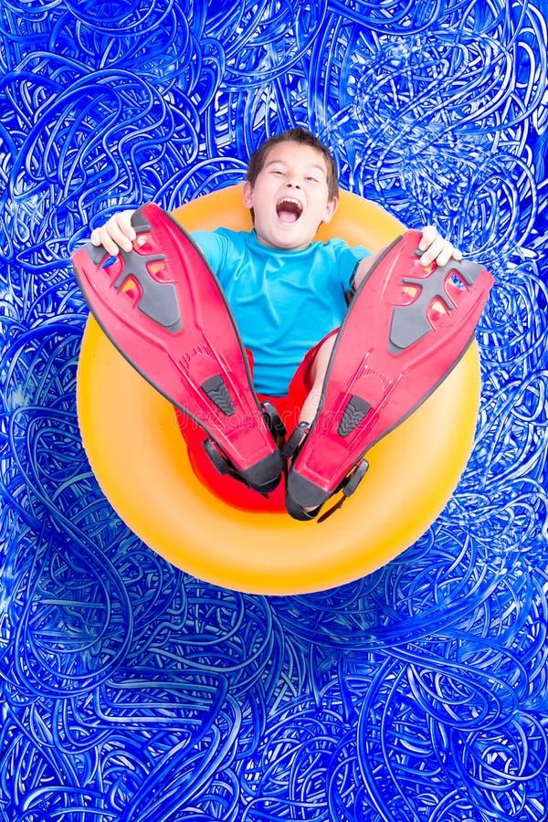 Ung pojke i flipper som spelar i en pöl fotografering för bildbyråer